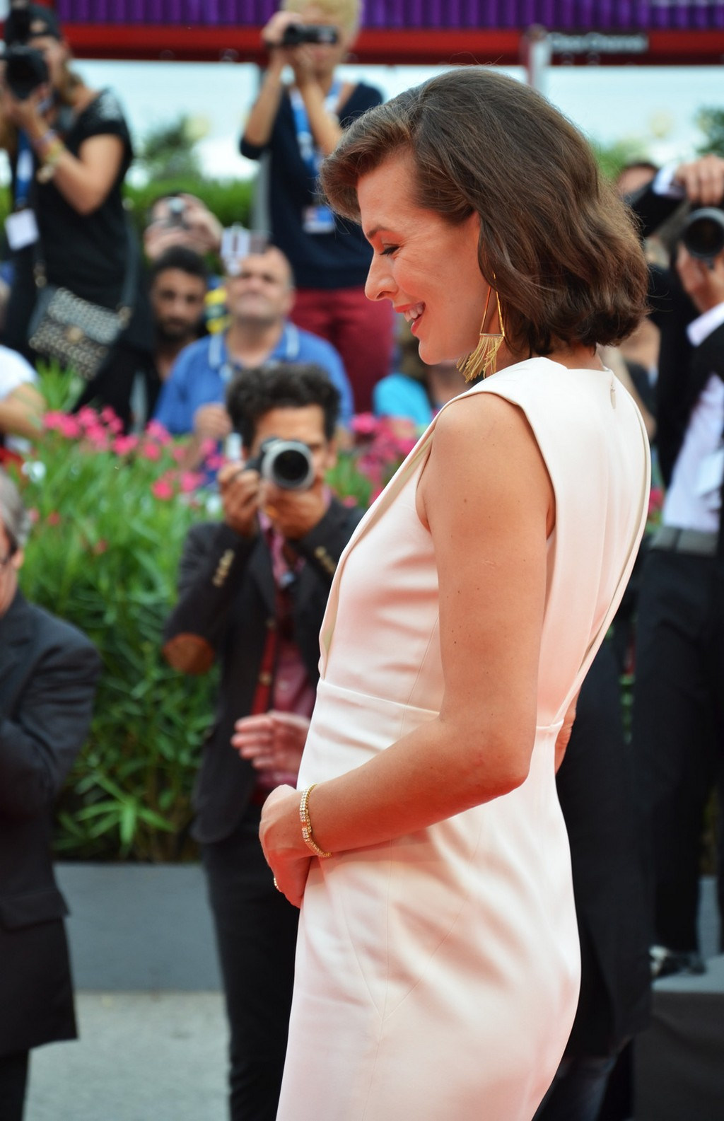 Mila Jovovich sul red carpet si pone una mano sul grembo a indicare la gravidanza, 71. Mostra d'Arte Cinematografica, Venezia 2014. Credits Valentina Zanaga
